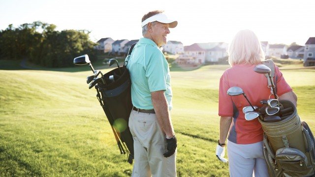 An older man and woman carrying golf bags without pain having received spine care from PT Central