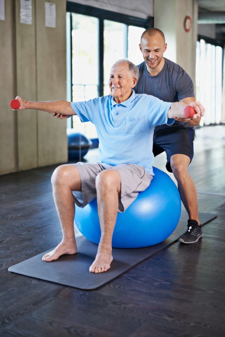 Man sitting on an exercise ball lifting weights for injury prevention