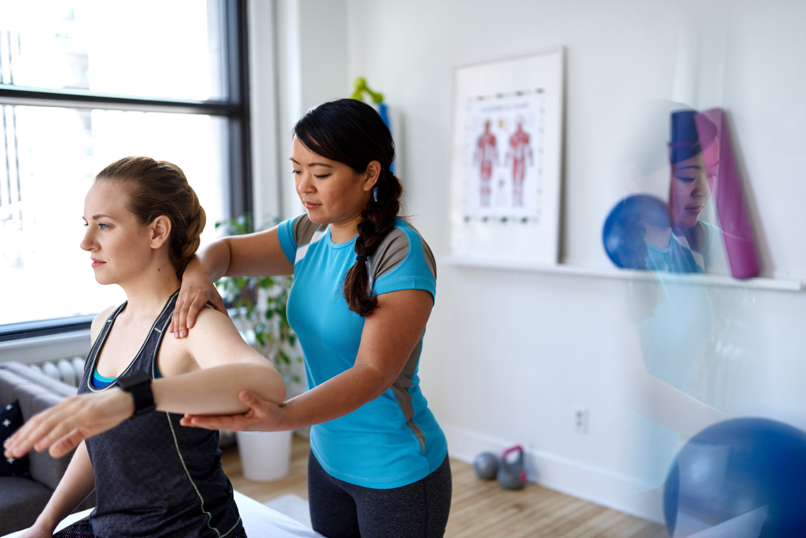 Candid image of an attractive patient during a appointment with professional asian physiotherapist in design kinesio clinic working and massaging her neck and shoulder pain